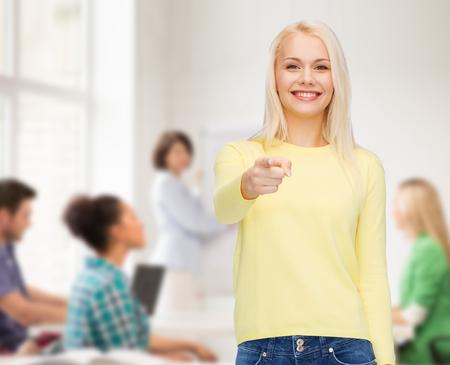invitando: felicidad, el gesto y el concepto de la gente - la mujer sonriente que señala el dedo en usted