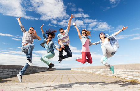 urban dance: summer, sport, dancing and teenage lifestyle concept - group of teenagers jumping Stock Photo