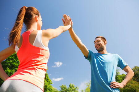sportive: fitness, sport, training and lifestyle concept - two smiling people making high five outdoors