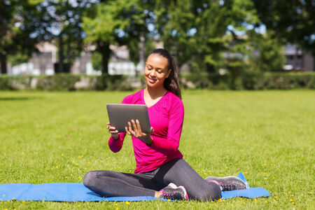 fitness, park, technology and sport concept - smiling african american woman with tablet pc computer sitting on mat outdoors photo