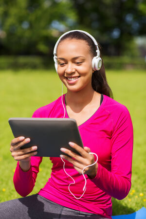 fitness, park, technology and sport concept - smiling african american woman with tablet pc computer and headphones on mat outdoors photo