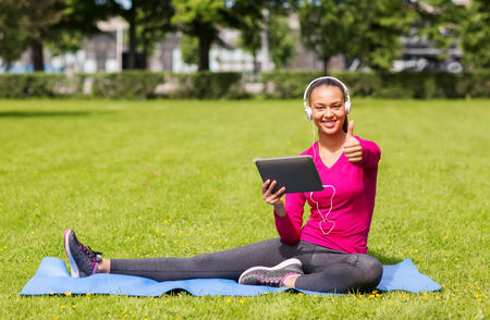 fitness, park, technology and sport concept - smiling african american woman with tablet pc and headphones showing thumbs up outdoors photo