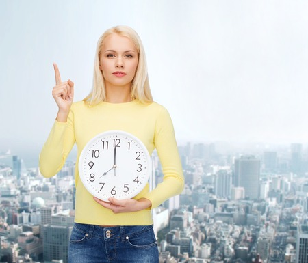 hurry up: time, education and people concept - serious young woman with wall clock showing 8 and finger up
