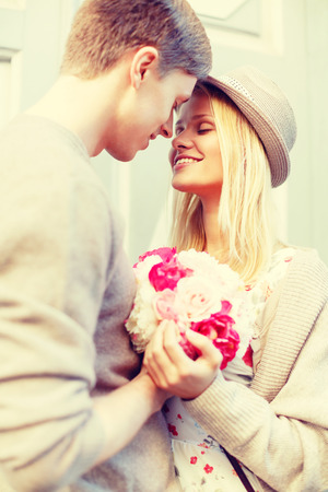 de zomer vakantie, liefde, relatie en dating concept - gelukkig paar met een boeket bloemen in de stad Stockfoto