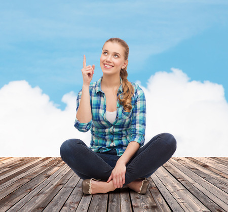 happiness, advertising and people concept - smiling young woman pointing finger up photo