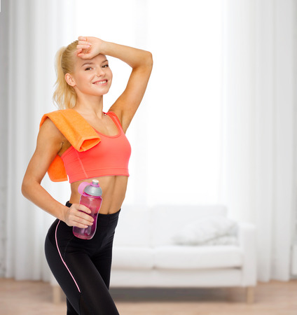 sport, exercise and healthcare - smiling sporty woman with orange towel and water bottle photo