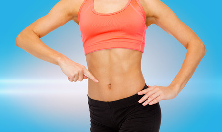 six packs: fitness, exercise and diet concept - close up of woman pointing finger at her six pack Stock Photo