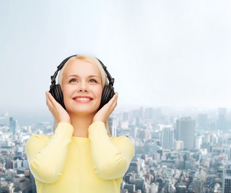 podcast: music and technology concept - smiling young woman listening to music with headphones