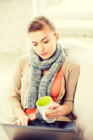 picture of diseased woman in scarf using laptop at home photo