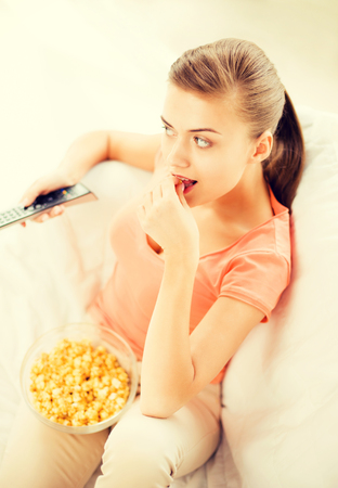 european food: picture of woman watching tv and eating popcorn
