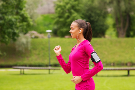 podcast: sport, fitness, health, technology and people concept - smiling young african american woman running with smartphone and earphones outdoors