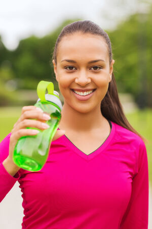 fitness, park, drink and sport concept - smiling african american woman drinking from bottle outdoors photo