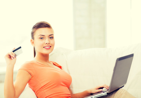 smiling woman with laptop showing credit card at home photo