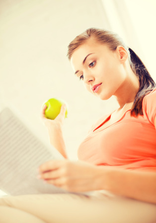 smiling woman with green apple reading magazine at home
