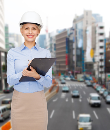 building, developing, construction and architecture concept - smiling businesswoman in white helmet with clipboard photo