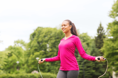 fitness, sport, training, park and lifestyle concept - smiling african american woman exercising with jump-rope outdoors