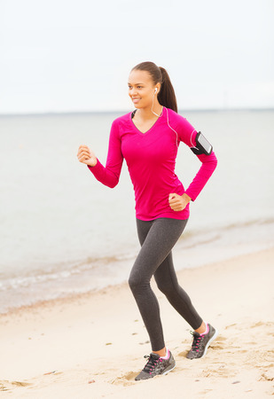 fitness, sport, training and lifestyle concept - smiling african american woman running with smartphone and earphones outdoors photo