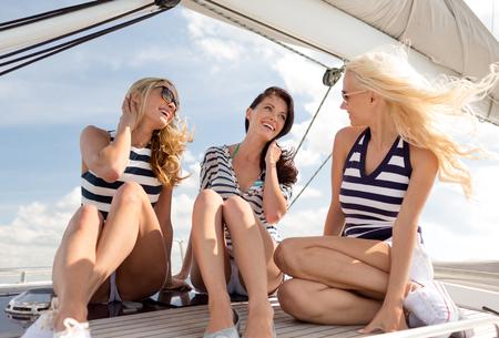 отдых, путешествия, море, дружба, и люди концепция - улыбается подруги, сидя на палубе яхты
