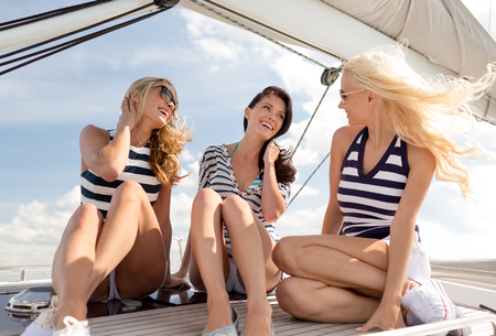 boat party: vacation, travel, sea, friendship and people concept - smiling girlfriends sitting on yacht deck