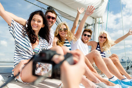 vacation, travel, sea, friendship and people concept - smiling friends sitting on yacht deck and photographing photo