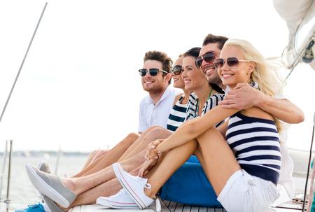 휴가, 여행, 바다, 우정과 명 개념 - 요트 갑판에 앉아 웃는 친구