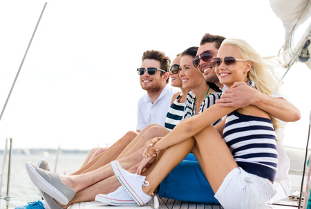 vacation: vacation, travel, sea, friendship and people concept - smiling friends sitting on yacht deck