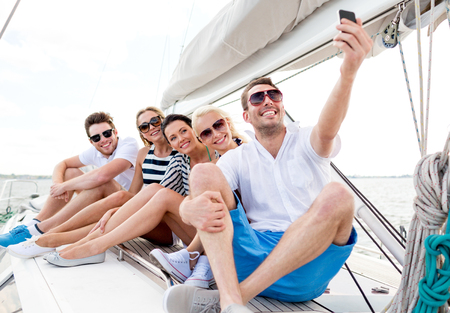 boat party: vacation, travel, sea, friendship and people concept - smiling friends sitting on yacht deck and making selfie