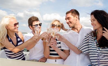 休暇、旅行、海、友情および人々 のコンセプト - 友達のヨットにシャンパンのグラスに笑顔