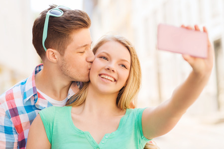 travel, vacation, technology and friendship concept - smiling couple with smartphone in city photo