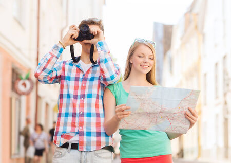 travel, vacation, technology and friendship concept - smiling couple with map and photo camera exploring city photo