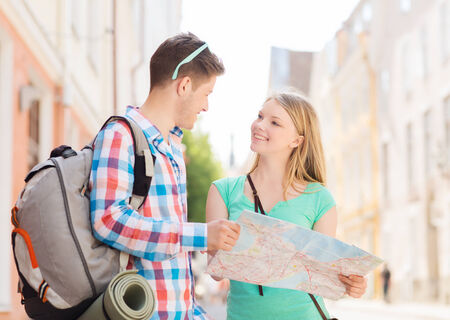 finding love: travel, vacation and friendship concept - smiling couple with map and backpack in city
