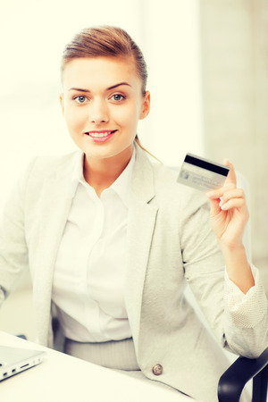 smiling businesswoman with laptop showing credit card photo