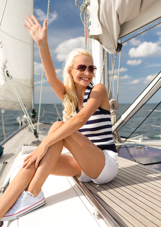 yacht people: vacation, holidays, travel, sea and people concept - smiling young woman sitting on yacht deck and greeting