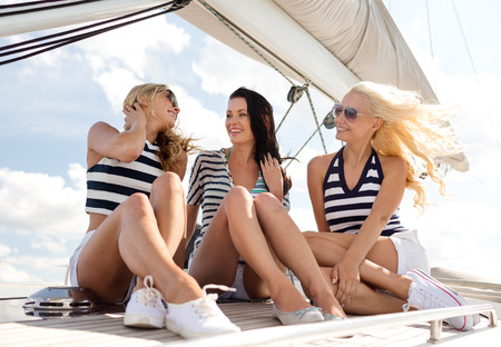 vacation, travel, sea, friendship and people concept - smiling girlfriends sitting on yacht deck photo