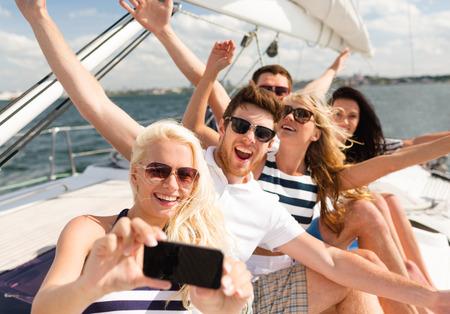 persona viajando: vacaciones, viaje, mar, la amistad y la gente de concepto - sonrientes amigos sentados en la cubierta del yate y haciendo selfie