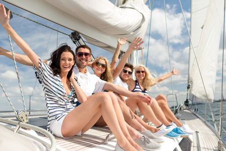 the yacht: vacation, travel, sea, friendship and people concept - smiling friends sitting on yacht deck and greeting