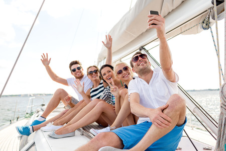 휴가, 여행, 바다, 우정과 명 개념 - 요트의 데크와 selfie을 만들기에 앉아 웃는 친구 스톡 콘텐츠