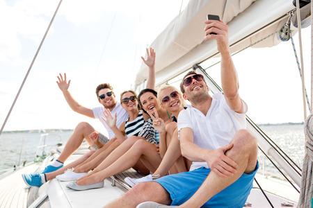 bateau voile: vacances, Voyage, mer, l'amitié et les concepts - souriant amis assis sur le pont de yacht et faire selfie