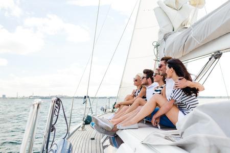 bateau voile: vacances, Voyage, mer, l'amitié et les concepts - souriant amis assis sur le yacht pont Banque d'images
