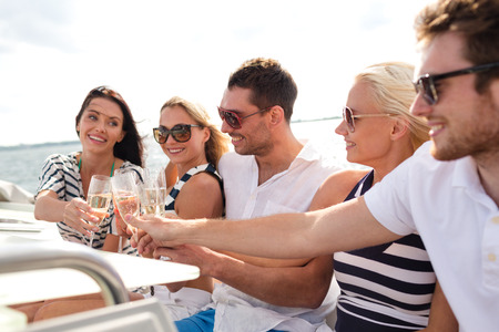 people   lifestyle: vacation, travel, sea, friendship and people concept - smiling friends with glasses of champagne on yacht