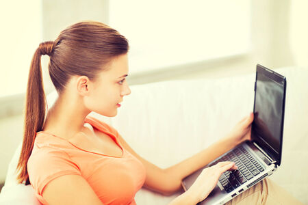 lifestyle and internet concept - woman using laptop at home photo