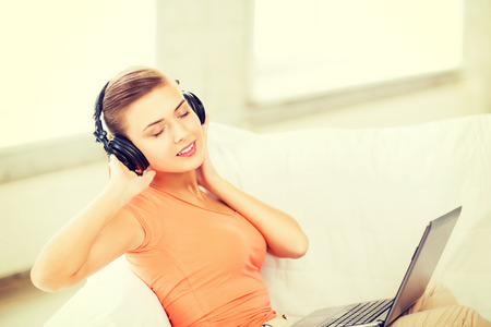 music, internet and shopping - woman with headphones and laptop at home photo