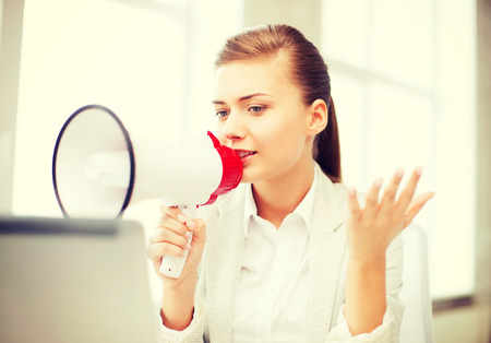 business concept - strict businesswoman shouting in megaphone in office photo