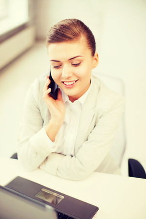 business and communication - smiling businesswoman with smartphone in office photo