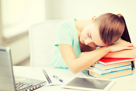 education and technology concept - tired student sleeping on stack of books photo