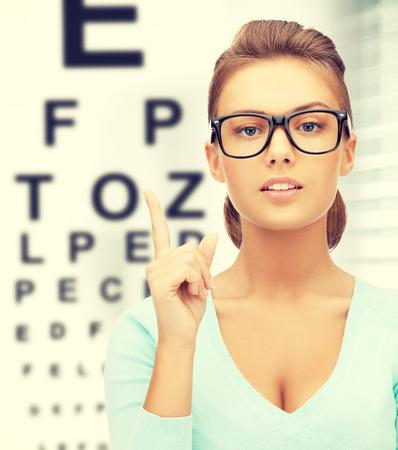 examen de la vista: la medicina y la visión concepto - mujer en lentes con la carta de ojo Foto de archivo