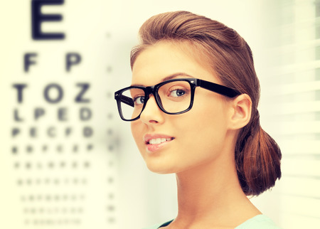 eye care: medicine and vision concept - woman in eyeglasses with eye chart Stock Photo