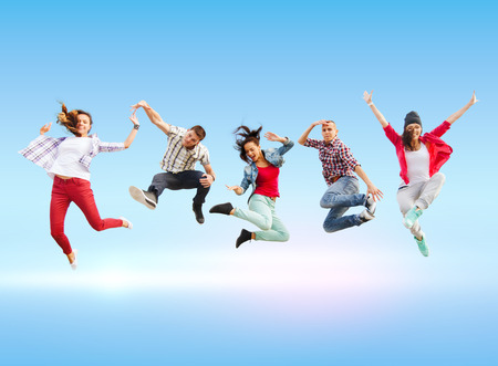 summer sport: summer, sport, dancing and teenage lifestyle concept - group of teenagers jumping Stock Photo