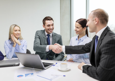 collaboration: business, technology and office concept - two smiling businessman shaking hands in office