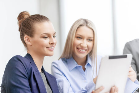 business, technology and office concept - smiling businesswomen with tablet pc computers having discussion in office photo
